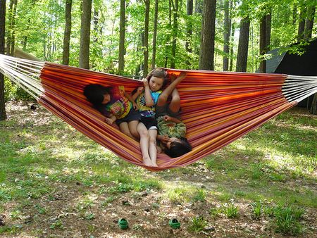 Children are using the hammock while camping in a trip to the fresh nature